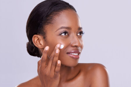 afro girl rubbing cream on her face