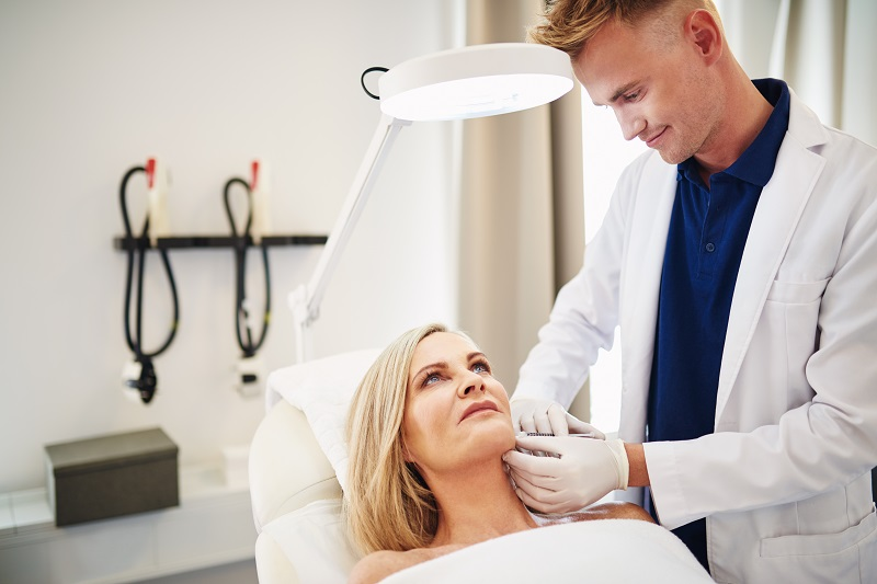 doctor injecting botox into a mature womans cheek YECRQV4